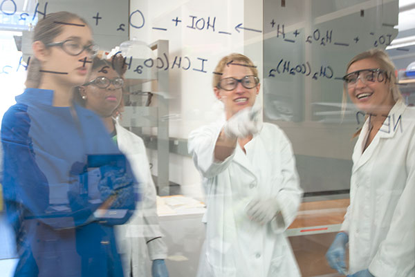 Photo of students analyzing a chemistry equation