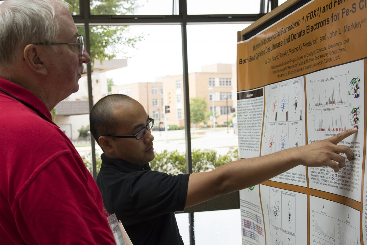 A student shows off his research poster to a faculty member.