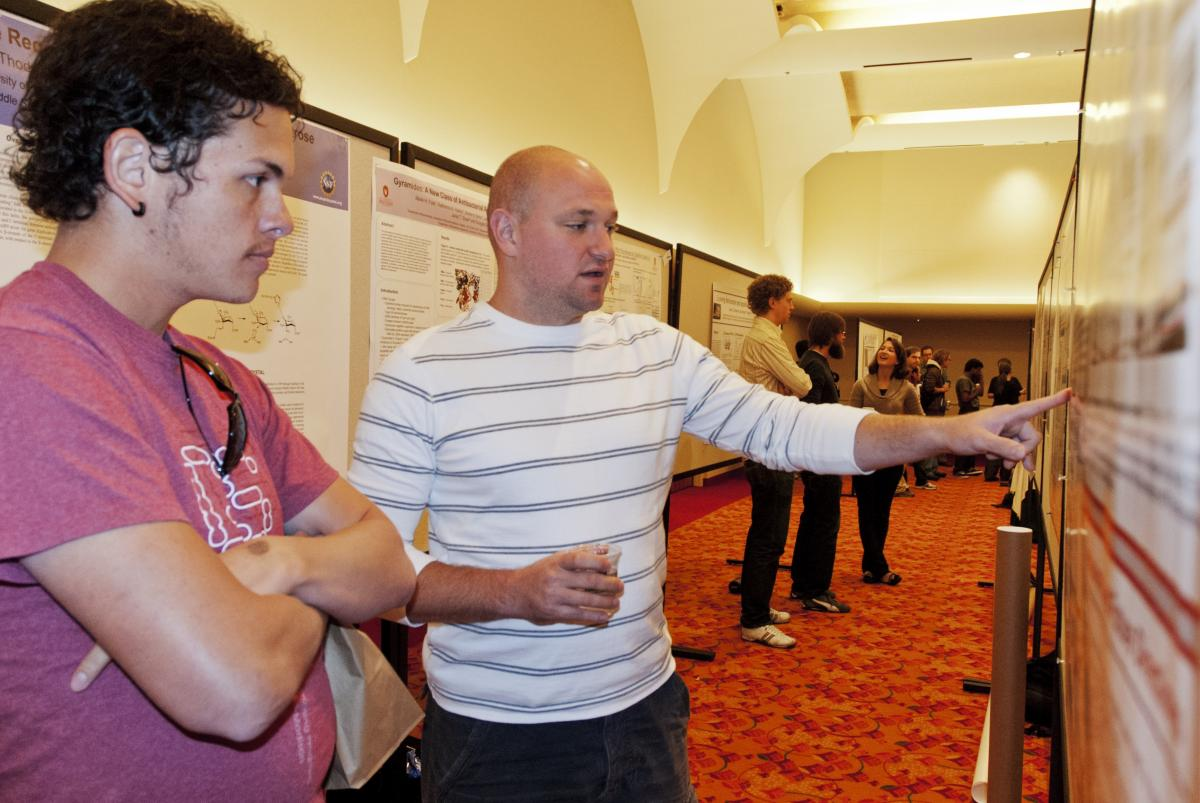 A photo from a past retreat. Two people look at a research poster.