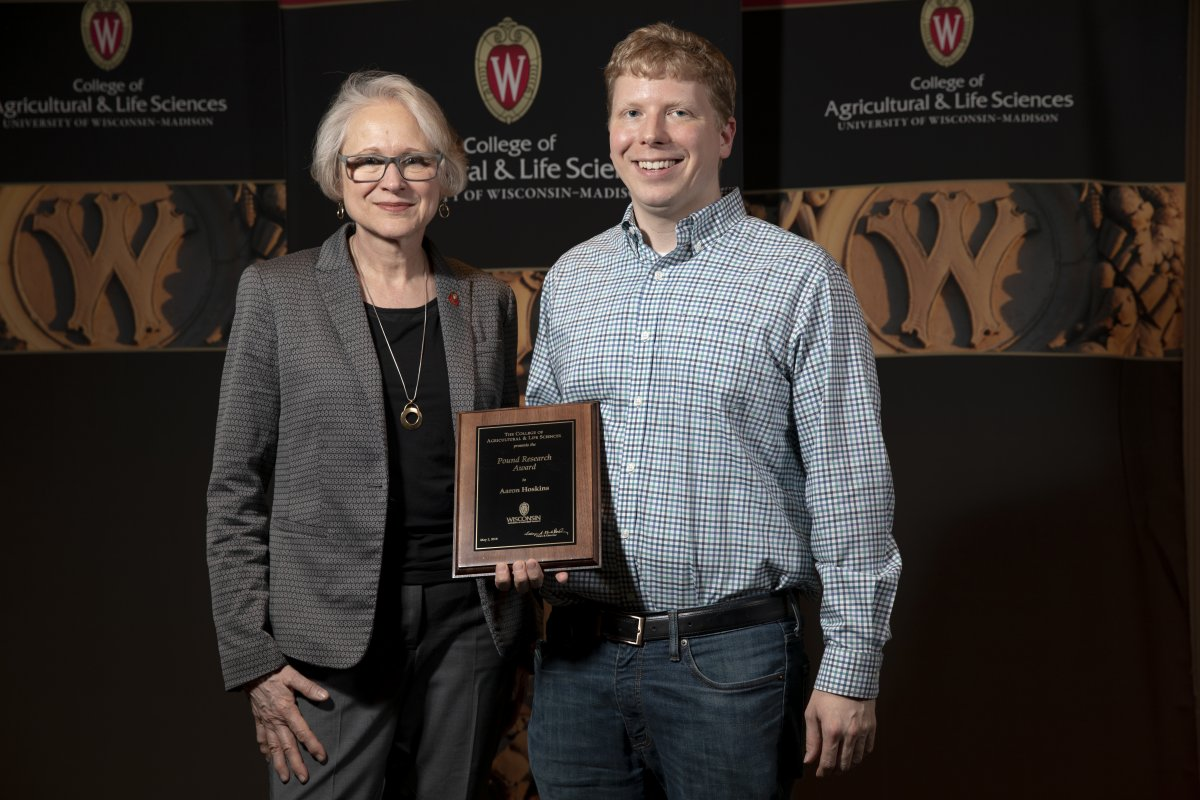 Biochemistry professor Aaron Hoskins poses with his award and the dean of the College of Agricultural and Life Sciences