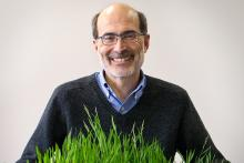 Professor Rick Amasino holds plants from his greenhouse